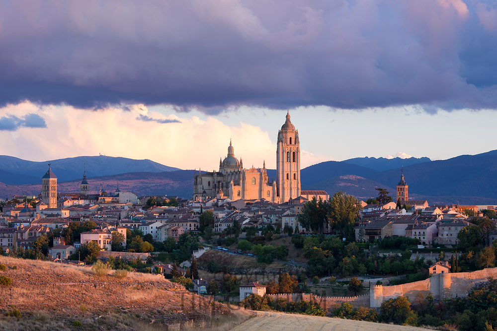 Famous view of Alcazar Castle - palace and fortress which inspired Disney castle, Cathedral and dramatic sky, Segovia, Spain