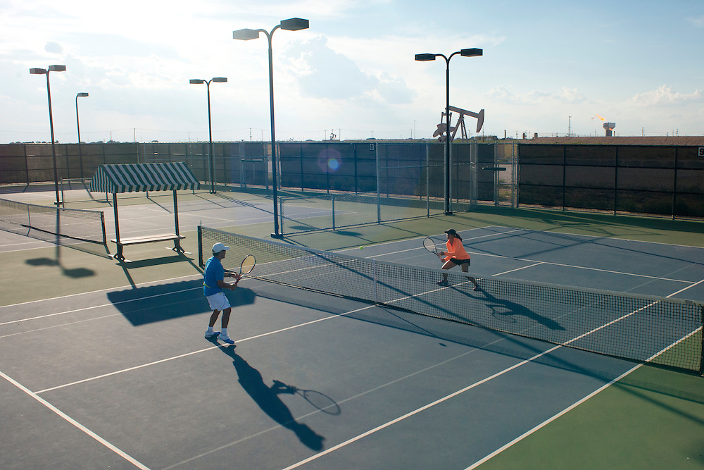Director of Tennis Luis Valdez trains with Olivia Baltazar, a member of the University of Texas of the Permian Basin tennis team, at the Bush Tennis Center in Midland, Texas on August 12, 2014. (Cooper Neill for The New York Times)