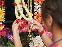 Young woman looking at artificial flowers necklaces back view selective focus
