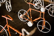 Men make miniature bicycles from metal wire at the Village Artisanal de Ouagadougou, a cooperative that employs dozens of artisans who work in different mediums, in Ouagadougou, Burkina Faso, on Monday November 3, 2008.