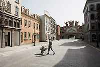 """ROME, ITALY -4 JULY 2014: A worker crosses the street with a barrow in the main promenade inspired after Martin Scorsese's """"Gangs of New York"""", right after the front gate of Cinecittà World, a theme park inspired by the film industry in Rome, Italy, on July 1st 2014<br /> <br /> The theme park is located just outside of Rome and features attractions from the mind of Oscar winning art director Dante Ferretti."""