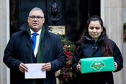 © Licensed to London News Pictures. 12/12/2017. London, UK. Bereaved residents from the Grenfell Tower tragedy Nicholas Burton and a girl who does not want to be named hand a petition in at Downing Street, calling for the public inquiry into the disaster to be overhauled. This includes having a panel from a diverse range of backgrounds installed alongside Sir Martin Moore-Bick, the retired Court of Appeal judge leading the process. Photo credit : Tom Nicholson/LNP