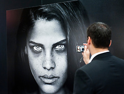 Man taking photo of black and white display image at Leica stand at Photokina digital imaging trade show in Cologne Germany 2010