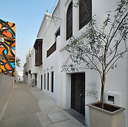 Abdullah Al Zayed House, an old traditional Bahraini house, restored and reopened in 2003 as the Abdullah Al Zayed House for Bahraini Press Heritage, as part of the Sheik Ebrahim Center, in Muharraq, Bahrain. On the left is a mural by eL Seed, a French Tunisian street artist. Muharraq is a city on the Pearling Path and with a strong history of pearl diving and pearl trade, where 17 buildings form part of a UNESCO World Heritage Site celebrating the pearl trade. Picture by Manuel Cohen