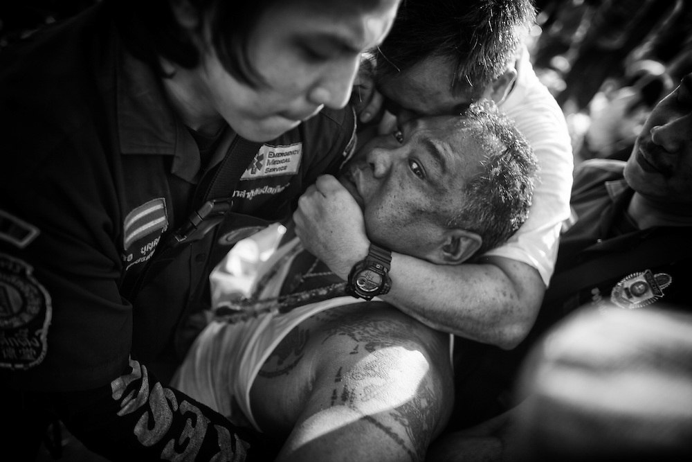 "A devotee in a trance is calmed by volunteers during the annual ""Wai Kru"" tattoo festival at Wat Bang Pra in Nakhon Chasi, Thailand Saturday, March 23, 2013.  Devotees attend the one day event to have their ""Sak Yant"" religious tattoos energized by Buddhist monks and tattoo masters."