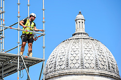 © Licensed to London News Pictures. 29/07/2020. LONDON, UK.  The dome of the National Gallery is seen behind a construction worker removing scaffolding around artist Heather Phillipson's 'THE END', which will soon be unveiled to the public as the new Fourth Plinth artwork in Trafalgar Square.  THE END will show a giant swirl of replica whipped cream topped with a cherry, a fly and a drone.  Its drone will transmit a live feed of the square which can be watched on a dedicated website.  The installation, originally planned for 26 March 2020, but postponed due to the coronavirus pandemic will remain on display for the next year two years.  Photo credit: Stephen Chung/LNP