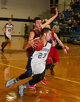 Winnisquam's Christian Serrano charges past Belmont's Chris Duggan during the boys semi final in the 41st annual Holiday Basketball Tournament at Gilford High School.  (Karen Bobotas/for the Laconia Daily Sun)