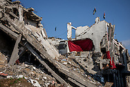 A partialy destroyed building in Shejaiya, red blankets are used to replace the missing walls. Two plaestinian flags and an Hamas one have been placed on the top of the building