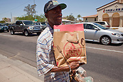 "22 JUNE 2009 - PHOENIX, AZ: Shawn Cooper, who is known on the street as ""Zero,"" walks back to the Veterans' Administration hospital after picking up some food at the Cultural Cup Food Bank. Zero, an unemployed Army vet, was referred to the food bank by workers at the VA. He said he wouldn't be able to eat regularly without the food bank's help. The Cultural Cup has become a sort of community center. It started as a food bank and has since grown to include a clothing bank and free walk in clinic. The walk in clinic at the Cultural Cup Food Bank started two years ago when Cultural Cup founder Zarinah Awad wanted to expand the food bank's outreach and provide basic medical care for the people who use the food bank. The clinic sees, on average, 7 - 11 patients a week. Awad said that as the economy has worsened since the clinic opened and demand has steadily increased. She attributes the growth to people losing their jobs and health insurance. The clinic is staffed by volunteers both in the office and medical staff. Adults are seen every Saturday. Children are seen one Saturday a month, when a pediatrician comes in. Awad, a Moslem, said the food bank and clinic are rooted in the Moslem tradition of Zakat or Alms Giving, the giving of a small percentage of one's income to charity which is one of the Five Pillars of Islam.   PHOTO BY JACK KURTZ"