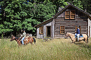 Horseback trail ride past log cabin
