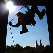 Syracuse, NY / 2003 - Firefighter David Hook performs rappelling exercises at a specialized five-story training tower in Syracuse.  The Sacred Heart Basilica appears in the background against a clear blue autumn sky. Photo by Mike Roy