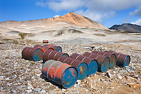 Fuel drums abandoned by miners and left to rust and leak into the wilderness watershed of Salal Creek, Ochre Mountain 2530 m (8301 ft) is in the distance. Coast Mountains British Columbia