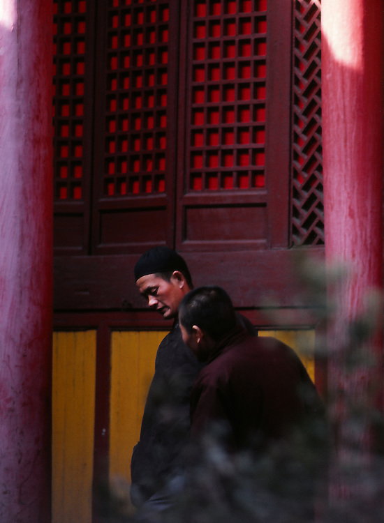 Two taoist monks having a discussion in the the courtyard of a temple, central China.