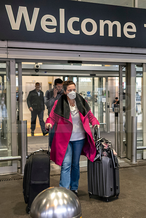 © Licensed to London News Pictures. 26/01/2020. London, UK. Passengers with protective masks at Heathrow Terminal 4 as signs have been installed around the terminal warning passengers of the symptoms of the new Wuhan coronavirus outbreak. The coronavirus virus has infected more than 10000 people across Asia in the past few weeks Photo credit: Alex Lentati/LNP