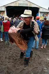 03 May 2013. New Orleans, Louisiana,  USA. .New Orleans Jazz and Heritage Festival. .JazzFest turns into a mud-fest following the recent heavy rains and flooding in the region. A couple dance in the dirt..Photo; Charlie Varley.