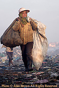 A worker at the Stung Meanchey Landfill in Phnom Penh, Cambodia, carries sacks of recyclable material across the dumpsite. She is one of 2000 people who earn livings as scavengers at the landfill.