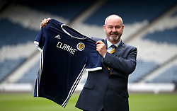 New Scotland manager Steve Clarke holds up a shirt during the press conference at Hampden Park, Glasgow.