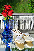 Red roses and ballet slippers with a weathered piano keyboard background, photographed outdoors on a mirror. It's a nice, happy splash of red, white, and blue to celebrate dance in an image. <br />