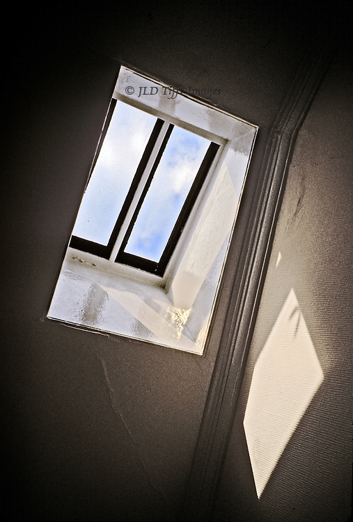 Geometric patterns of rectangles from sun and shadows cast on the attic walls of a 19th century late Georgian house in Edinburgh.  Blue sky and white fluffy clouds visible through the glass.  Point of view looking upward