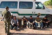 30 MARCH 2004 -- NACO, AZ: A US Border Patrol agent writes up undocumented immigrants apprehended in the San Pedro River bed near Naco, AZ. PHOTO BY JACK KURTZ
