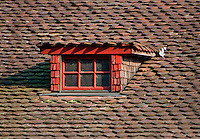 Detail of an old tiled roof and red window frame at Lenzburg Castle, Switzerland.