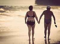 An elderly couple hold hands while taking a walk on Mui Ne Beach, Vietnam, Southeast Asia in April, 2008.