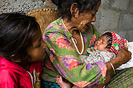 Monika (7, in red) watches as her grandmother Bhagawati Baniya (56) cradles her youngest sister Sapana Baniya (2 months) in their temporary home in Chautara, Sindhupalchowk, Nepal on 29 June 2015. The three girls lost their mother during the April 25th earthquake that completely levelled their house. Aastha was buried under the rubble together with her mother but Aastha survived. As their father Ratna Baniya (28) cannot care for the children on his own, SOS Childrens Villages has since been supporting the grandmother with financial and social support so that she can manage to raise the children comfortably and ensure that they will all be schooled. Photo by Suzanne Lee for SOS Children's Villages