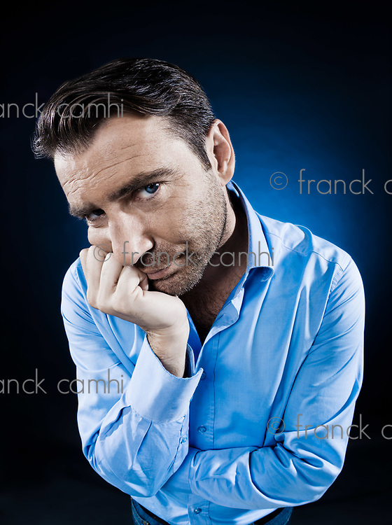 caucasian man unshaven portrait sulk bored isolated studio on black background