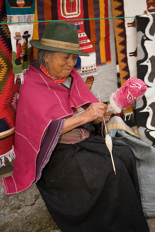 South America, Ecuador, Saquisili, woman in traditional clothing spinning wool at weekly food and crafts market which draws indigenous people and tourists from surrounding villages