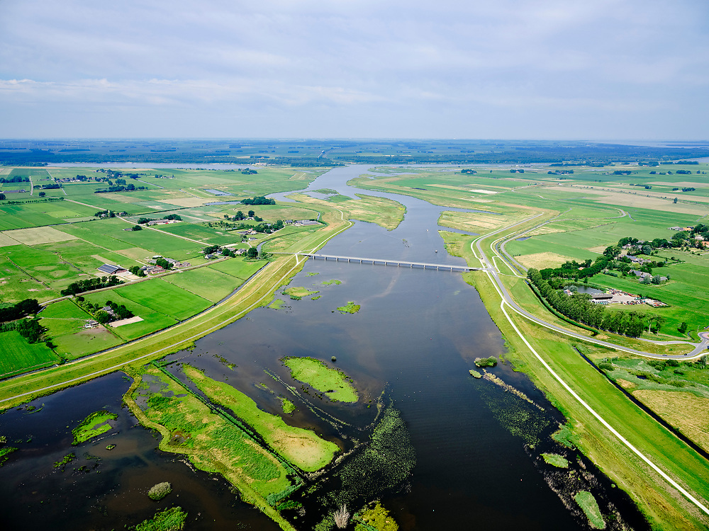 "Nederland, Overijssel, Gemeente Kampen; 21–06-2020; het Reevediep richting monding in het Revemeer (voorheen Drontermeer), Flevoland aan de horizon. In het midden  de Nieuwendijkbrug, met deel van De Enk in de voorgrond. Voor de aanleg van het Reevediep liep ter hoogte van dit natuurgebied in Kamperveen het riviertje Reeve.<br /> Het Reevediep is aangelegd in het kader van het project Ruimte voor de Rivier om bij hoogwater water af te voeren voordat dit het nabij gelegen Kampen bereikt, direct naar het IJsselmeer, de 'bypass Kampen'. Het Reevediepgebied is ook een natuurgebied en vormt een ecologische verbindingszone tussen rivier de IJssel en Drontermeer.<br /> Reevediep towards the mouth in the Revemeer (formerly Drontermeer). The Nieuwendijkbrug, Flevoland on the horizon.<br /> The Reevediep has been constructed as part of the Room for the River project, and functions to discharge high waters before reaching the nearby Kampen, directly to the IJsselmeer, the ""bypass Kampen"". The Reevediep area is also a nature reserve and forms an ecological connecting zone between the river IJssel and Drontermeer.<br /> <br /> luchtfoto (toeslag op standard tarieven);<br /> aerial photo (additional fee required)<br /> copyright © 2020 foto/photo Siebe Swart"