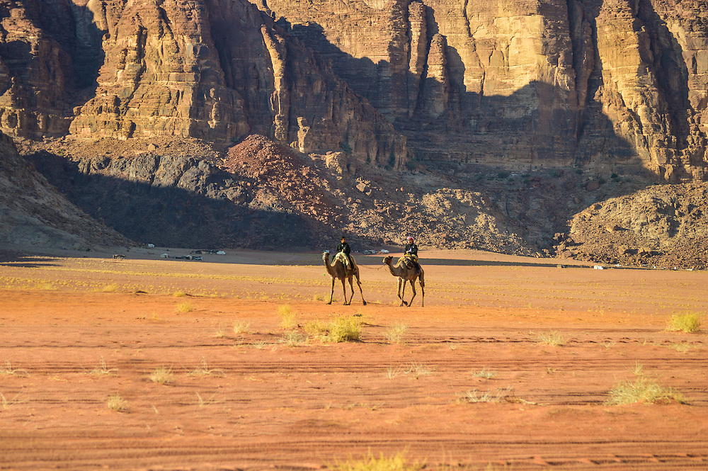 Two Bedouins riding their camels.