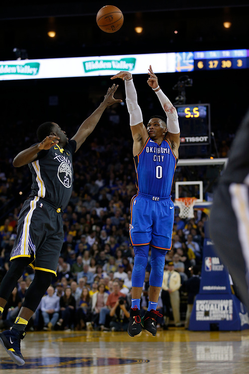 Oklahoma City Thunder guard Russell Westbrook (0) shoots against Golden State Warriors forward Draymond Green (23) during the second half of an NBA game between the Warriors and Oklahoma City Thunder at Oracle Arena, Tuesday, Feb. 6, 2018, in Oakland, Calif. The Warriors lost 105-125.