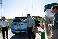 Ian Sutherland, from General Motors research and development in Warren Michigan (right) looks on as Millennium Reign Energy LLC CEO Chris McWhinney shows the key that is needed to transfer Hydrogen from the renewable hydrogen station to the GM fuel cell car during a demonstration at the Dull Family Homestead, which has a fueling station made by Millennium Reign Energy LLC, Saturday, October 15, 2011. This station is a private one, for demonstration and testing of the concept, but McWhinney says it's an example of how future filling stations may work.  The wind turbines behind and above McWhinney help to generate the hydrogen that powers the car.