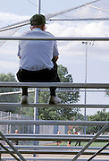 Elderly man seated on bleachers