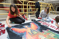 Students painting Homecoming banners in Crown Fieldhouse