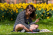 A woman carries out a business call, Ignoring Governement advice and enjoying the sun in Green Park - A sunny day and people are out in reasonable numbers, throughout London, to get their daily exercise.  The 'lockdown' continues for the Coronavirus (Covid 19) outbreak in London.