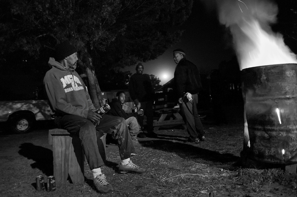 On a chilly October night, Geechee men hang out by a fire outside of the Graball County Store, the only convenience store and one of the few businesses in the Hog Hammock community.