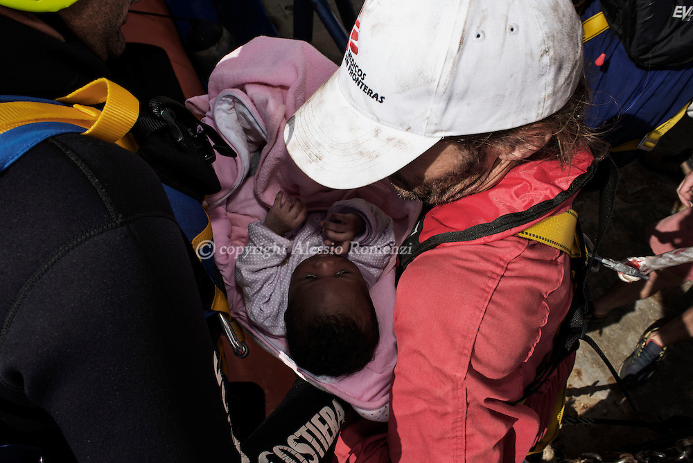 Italy: MSF Dignity1: Italian coast guard officials and MSF members take care of an African migrant child rescued at sea on the Dignity1 on August 23, 2015. Alessio Romenzi