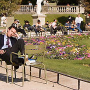 Man naps in chair in the Jardin du Luxembourg, Paris France<br />
