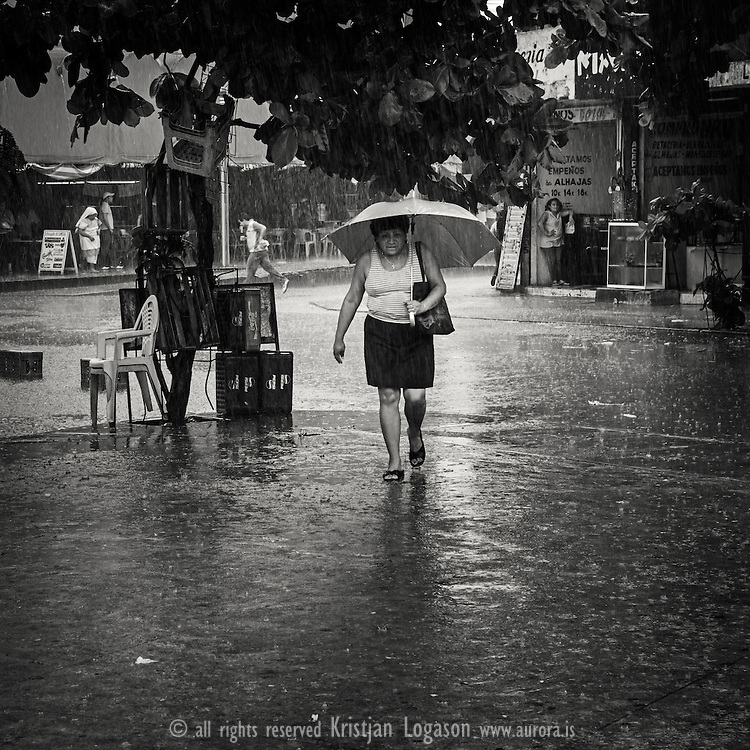 Woman with an umbrella crossing a street in the heavy rain hitting  Merida that day