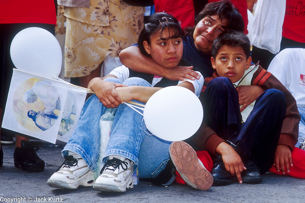 """jku032303057 - 31 JULY 2002 - MEXICO CITY, DF, MEXICO: A family on the Zocalo in the historic center of Mexico City watches a Papal mass televised to the Zocalo on large screen """"jumbotron"""" televisions. The mass, led by Pope John Paul II, was at the Basilica of Guadalupe in Mexico City, July 31, 2002. The Pontiff, making his fifth trip to Mexico, canonized Juan Diego, the Mexican Indian who first saw the image of the Virgin of Guadalupe in 1531. Juan Diego is now known at Saint Juan Diego. PHOTO © JACK KURTZ  RELIGION  INDIGENOUS  CULTURE  PATRIOTISM"""