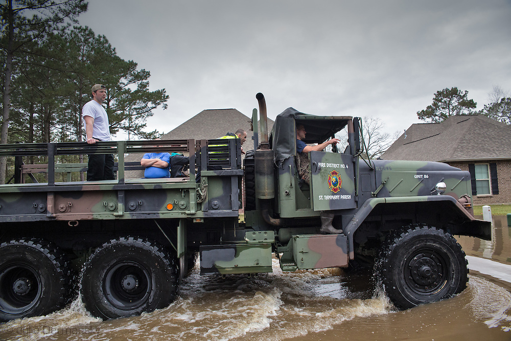Covington Louisiana, March, 12, 2016,  The Louisiana National Guard use a truck to evacuate residents for the Tallow Creek subdivision. 14 inches of rain fell in less than 24 hours, after three days of intermittent rain, causing flash floods. The Tchefuncte River  and Bogue Falaya River<br />  crested on Saturday morning but the flood event continued into the night for those in Tallow Creek.