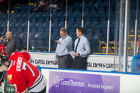 KELOWNA, CANADA - MARCH 3: Portland Winterhawks' coaches Don Hay and Kyle Gustafson share a laugh on the bench during warm up against the Kelowna Rockets on March 3, 2019 at Prospera Place in Kelowna, British Columbia, Canada.  (Photo by Marissa Baecker/Shoot the Breeze)