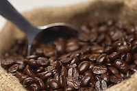 Sack of coffee beans with spoon, close-up