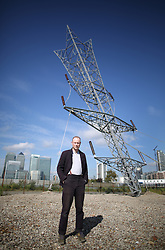 © Licensed to London News Pictures. 17/09/2015. London, UK. Artist Alex Chinneck stands with his newly unveiled 35 metre high sculpture entitled 'A bullet from a shooting star'.  Depicting an inverted electricity pylon, the artwork is located on Greenwich Peninsula. Photo credit: Peter Macdiarmid/LNP