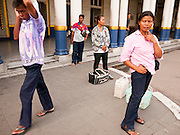 11 JULY 2011 - BANGKOK, THAILAND:   People wait for taxis in front of Hua Lamphong train station in Bangkok. Hua Lamphong Grand Central Railway Station, officially known as the Bangkok Grand Central Terminal Railway Station, is the main railway station in Bangkok, Thailand. It is located in the center of the city in Pathum Wan District, and is operated by the State Railway of Thailand. The station was opened on 25 June 1916, after six years' construction. The station was built in an Italian Neo-Renaissance style, with decorated wooden roofs and stained glass windows. The architecture is attributed to Turin-born Mario Tamagno, who, with countryman Annibale Rigotti made a mark on early 20th century public building in Bangkok. The pair also designed Bang Khun Prom Palace (1906), Ananda Samakhom Throne Hall in The Royal Plaza (1907-15) and Suan Kularb Residential Hall and Throne Hall in Dusit Garden, among other buildings..There are 14 platforms and 26 ticket booths. Hua Lamphong serves over 130 trains and approximately 60,000 passengers each day. Thailand has the most advanced rail system in Southeast Asia and trains from Hua Lamphong serve all corners of the Kingdom.        PHOTO BY JACK KURTZ