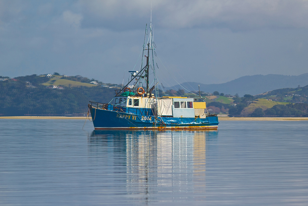 an hdr image of a fishing boat. i love fishing boats and the stillness with the reflection off the water cried out for hdr.