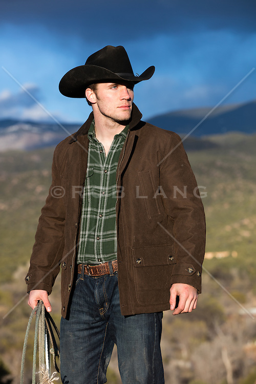 cowboy holding a lasso overlooking a mountain range