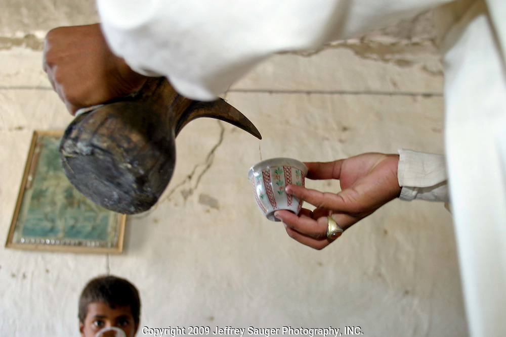 A young man from the village serves coffee at the Al-kasid family's Istikbal, or homecoming, in their home village Suq ash Shuyukh about 20 miles southeast of Nasiriyah, Iraq, Tuesday, July 29, 2003. The boys work throughout the 3 day celebration fetching water, serving food, cleaning, etc., which teaches them respect for their elders. In return, they are fed better than normal and get to be a part of the action as this was a huge event in the village...When Malik Al-kasid's caravan approached, guns were fired to announce his family's arrival. The welcming party then, returns fire to welcome him. The two parties move toward each other dancing and shooting until they join in the middle where the Hawaies occurs. ..The Al-kasid family fled Iraq after the Gulf War and their part in the uprising against Saddam Hussein in 1991, spent 3 years in Rafa, Saudi Arabia and finally settled in Dearborn, MI. The family hasn't been home to Iraq in 13 years.