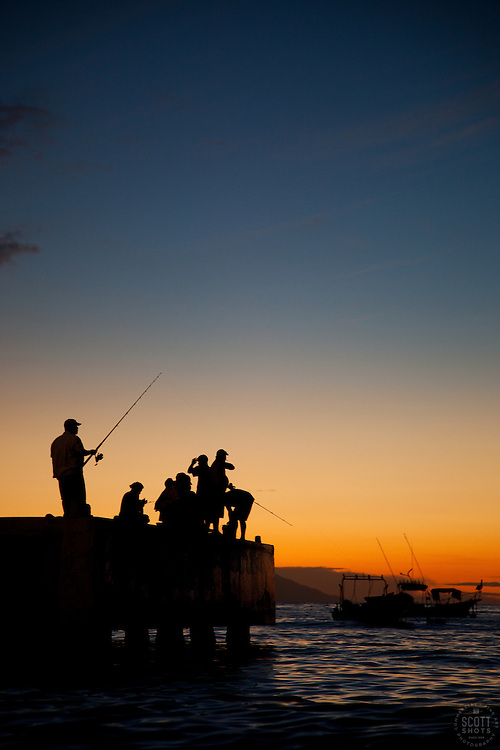 """""""Fishermen at Sunset"""" - These men fishing on a pier were photographed at sunset in Puerto Vallarta, Mexico."""